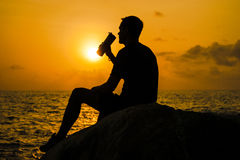 The man drinks from a bottle at dawn Royalty Free Stock Photography