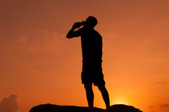 The man drinks from a bottle at dawn Royalty Free Stock Images