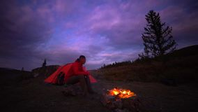 Man drinks at camp fire. Life on travel, evening time. Orange tent and backpack are behind a man stock video footage