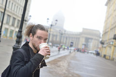 Man drinks coffee in cold weather outside. Stock Photos