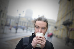 Man drinks coffee in cold weather outside. Stock Images