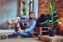 A man drinks coffee in a room with loft interior. Stock Photography