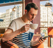 Man drinks coffee from the white cup of tea Royalty Free Stock Images