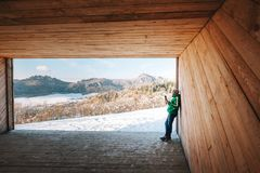 Man drinks a hot drink in wooden hangar with mountains panorama. View Stock Photo