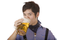 Man drinks out of Oktoberfest beer stein (Mass). Closeup of handsome young man drinking beer out of beer stein. Isolated on white Royalty Free Stock Photo