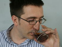 Man Drinks Swig Of Brandy. Adult man with glasses drinking brandy, blue background Stock Photo