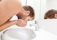 Man drinks tap water. From the bathroom sink stock images