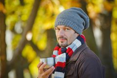 Man drinks tea in autumn park Stock Photo