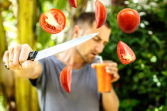 Man drinks tomato juice and cuts tomatoes simultaneously. Royalty Free Stock Photos