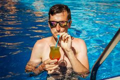 Man drinks tropical cocktail in swimming pool. All inclusive concept. MHandsome young man drinks tropical cocktail in swimming pool. All inclusive concept Stock Photos