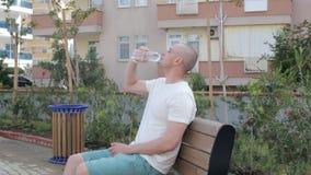 Man drinks water outdoor stock video