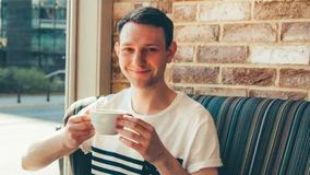 Man drinks the white cup of black coffee and he is happy Royalty Free Stock Photography