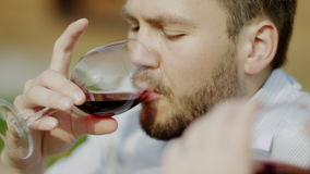 Man drinls wine with his girlfriend. Serious man clinking glasses and drinking red wine with his girlfriend on a picnic stock footage
