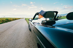 Man drive cabriolet car on province mountain road Stock Images