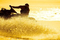 Man drive on the jetski. Strong man drive on the jetski above the water at sunset .silluet. spray Stock Images