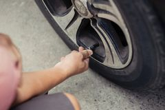 Man driver checking air pressure and filling air in the tires of Stock Photography