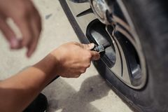 Man driver checking air pressure and filling air in the tires of Royalty Free Stock Photos