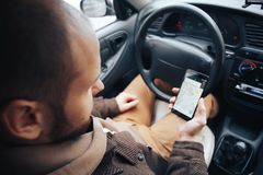 Man driver holding mobile phone with gps application in his car, modern navigation technology for travel and driving concept stock photography