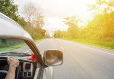 Man driver holding steering wheel right on rural road Stock Image