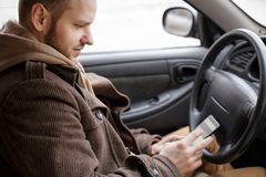 Man driver using smart phone in car, internet technology communication on road royalty free stock photo