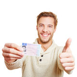 Man with drivers licence holding. Happy man with his European drivers licence holding his thumbs up stock photography