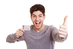 Man with drivers license. Cheering young man with his European driving license holding a thumb up Stock Image