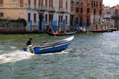 Man drives the blue motorboat with wooden chest. Small DOF. Venice, Italy - August 21, 2015: Man in headphones listens to music and drives the blue motorboat royalty free stock photo