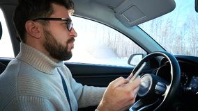 A man drives a car in winter on the highway between cities. He writes a message in the smartphone and is distracted from