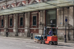 Man drives a forklift truck outside Smithfield Market. LONDON, UK - MAY 12, 2016:  Man drives a forklift truck outside Smithfileds Market in Farringdon area Royalty Free Stock Photography