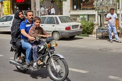 Man drives his wife and son on motorcycle, Kashan, Iran. Kashan, Iran - April 27, 2017: A family of three Iranians, father, mother and son, a teenager, ride a Stock Photo