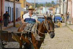 Man drives horse driven carriage at the street of Trinidad town, Cuba. Royalty Free Stock Images