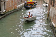 Man drives the motor boat in the Venetian canal, Italy Royalty Free Stock Photo