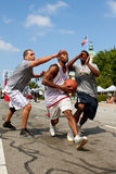 Man Drives To The Basket In Outdoor Street Basketball Tournament. Athens, GA, USA - August 24, 2013:  A young man splits two defenders while driving to the hoop Royalty Free Stock Photo