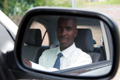 Man driving. An african man is driving a car and looking into the side mirror Royalty Free Stock Photography
