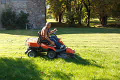 Man Driving A Red Lawn Mower (tractor) Royalty Free Stock Image