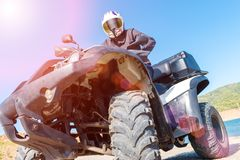 A man is driving ATV on off-road. Sunny royalty free stock images