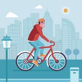 Man Driving Bicycle on Modern City. Smiling man on bicycle driving on modern city background. Cyclist guy riding red bike on the road. City bike rental service Royalty Free Stock Images