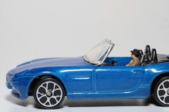Man driving a blue car. Miniature figurine of a man driving his car Royalty Free Stock Photography