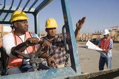 Man Driving Bulldozer With Co-Worker Stock Photos