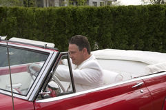 Man Driving Car. A sharp dressed man driving an old classic convertible car Stock Photos