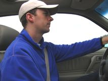 Man Driving Car. Photo of a man in blue jacket and hat driving a car Royalty Free Stock Images