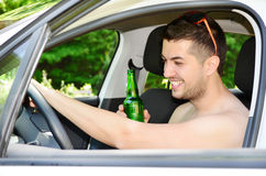 Man driving car with beer in hand Stock Image