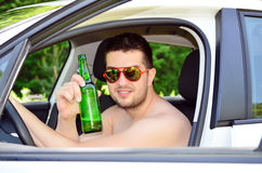 Man driving car with beer in hand Royalty Free Stock Photos