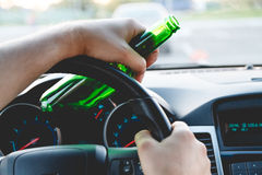 A man driving a car with a bottle of beer Royalty Free Stock Photo