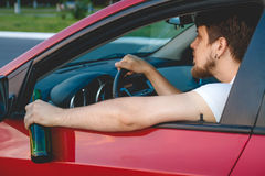 A man driving a car with a bottle of beer. Drunk young man driving a car with a bottle of beer. Don't drink and drive concept. Driving under the influence. DUI Royalty Free Stock Photos