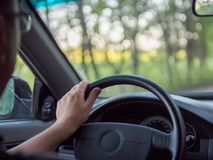 Man driving a car, close-up photo. The driver is holding the steering wheel. royalty free stock photo