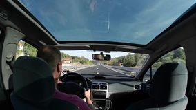 Man driving a car on country road stock footage