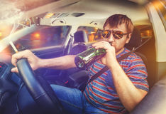 Man driving the car and drinking beer Stock Photography