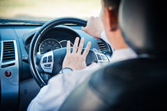 Man driving a car with hand on horn button Stock Images