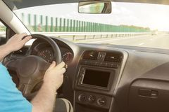 Man driving a car. hands on the handlebars. on a background of a road in sunset sun. Interior. Multimedia. Enjoyment from driving Stock Photography